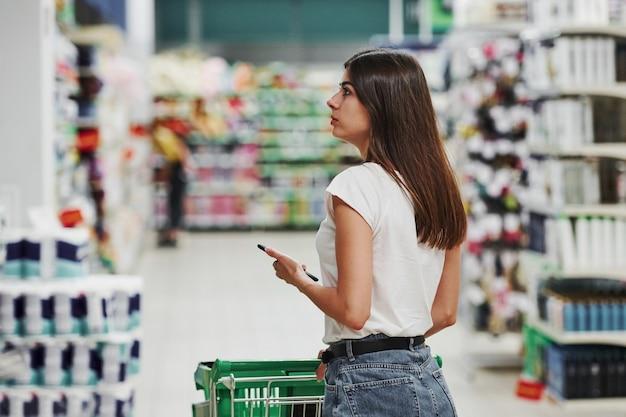 Weibliche käufer in freizeitkleidung im markt auf der suche nach produkten.
