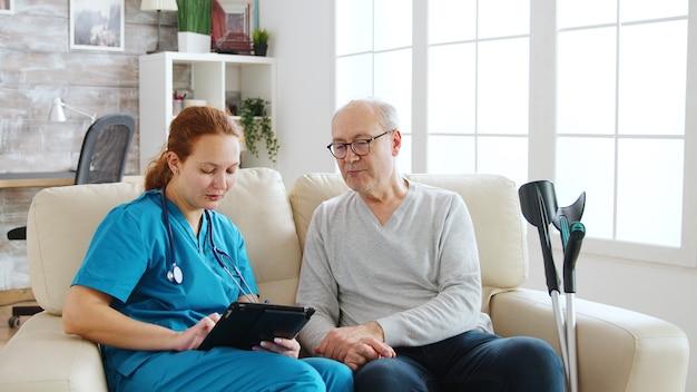 Weibliche kaukasische krankenschwester, die notizen über die gesundheit älterer männer in einem hellen und gemütlichen pflegeheim macht. betreuer und sozialarbeiter