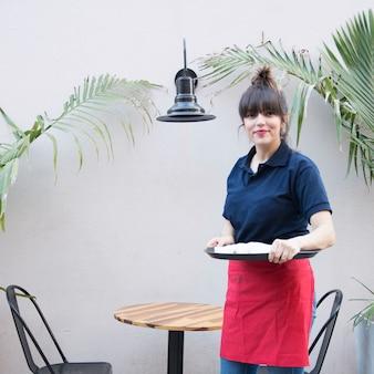 Weibliche kellnerin, die außerhalb des cafã © hält behälter steht
