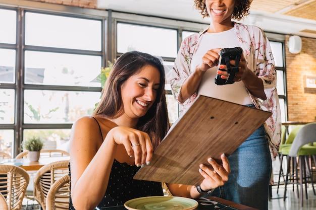 Weibliche kellnerin, die die bestellung auf smartphone im restaurant entgegennimmt