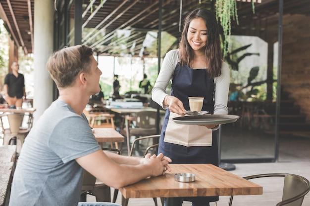 Weibliche kellnerin, die einem männlichen kunden kaffee serviert