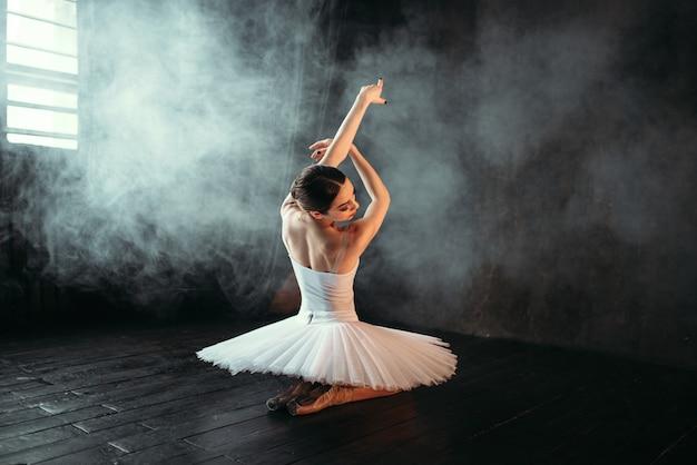 Weibliche klassische ballettdarstellerin im weißen kleid, das auf dem boden sitzt, rückansicht. ballerina training im unterricht mit fenster