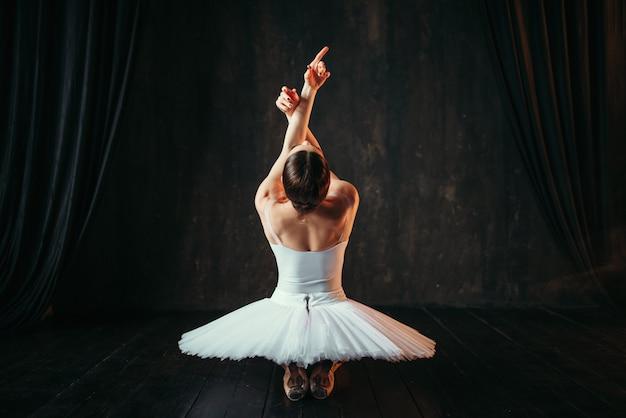 Weibliche klassische ballettkünstlerin, die auf boden sitzt