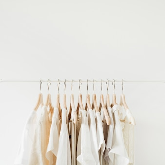 Weibliche kleidung auf kleiderbügel. minimale modekomposition auf weiß