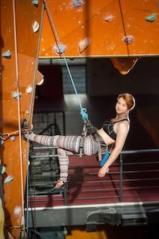 Weibliche kletterer klettert auf indoor kletterwand