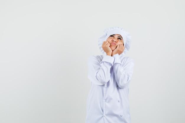 Weibliche köchin, die gesicht auf ihren händen in der weißen uniform kissen und hoffnungsvoll aussehend
