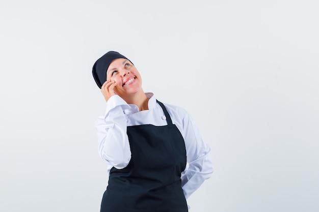 Weibliche köchin, die hand auf wange in uniform, schürze hält und verträumt aussieht. vorderansicht.