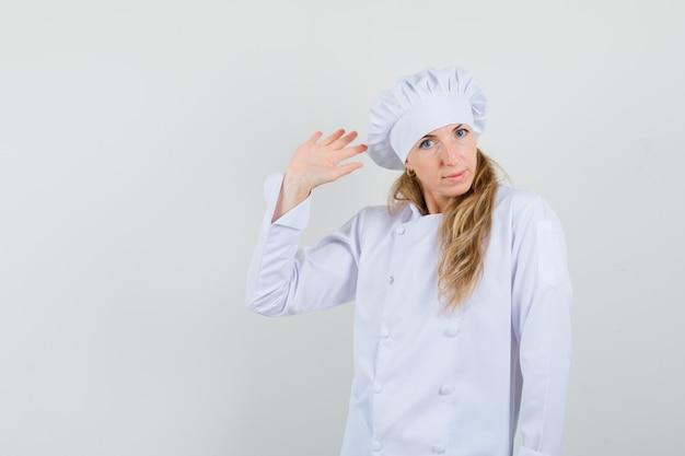 Weibliche köchin, die hand für gruß in der weißen uniform winkt und positiv schaut.