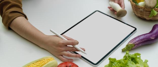 Weibliche köchin, die online zutaten auf tablett mit leerem bildschirm im küchenzimmer bestellt