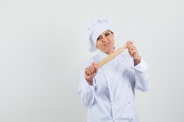 Weibliche köchin hält nudelholz in weißer uniform und sieht selbstbewusst aus.