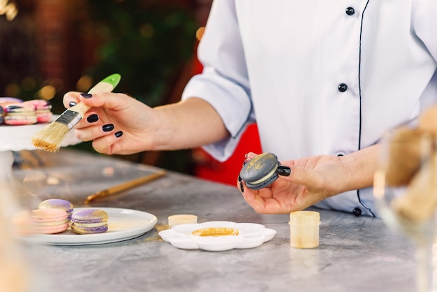 Weibliche konditorfarbe mit pinsel ein goldenes lebensmittel farb auf einem frischen macarons. frisch gebackene macarons zubereiten.