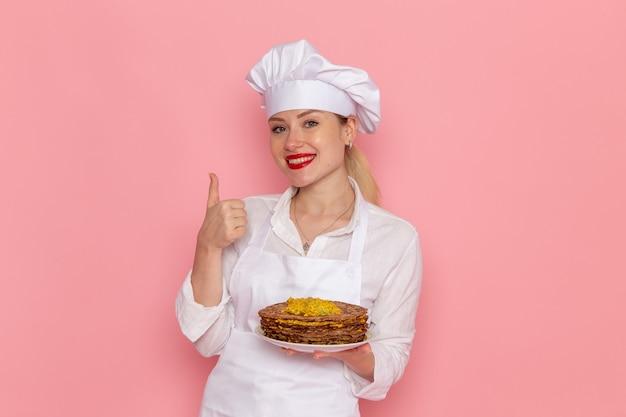 Weibliche konditorin der vorderansicht in der weißen abnutzung, die köstliches gebäck auf der hellrosa wand süßwaren süßes gebäckjobarbeit hält