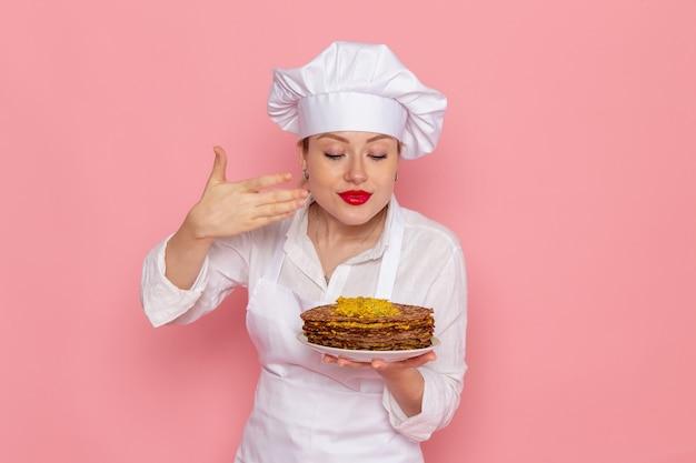 Weibliche konditorin der vorderansicht in der weißen abnutzung, die köstliches gebäck auf der rosa wandkonfekt süßes gebäckjobarbeit hält
