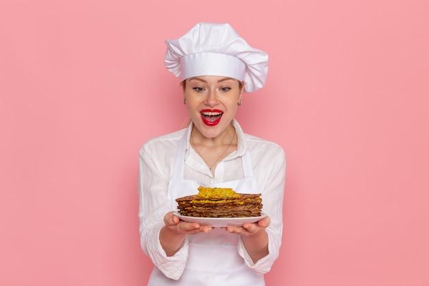 Weibliche konditorin der vorderansicht in der weißen abnutzung, die köstliches gebäck auf süßem gebäck der rosa wandkonfektion hält
