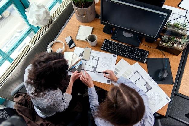 Weibliche konstrukteure diskutieren ein projekt und nehmen die endgültige korrektur der farbe im büro vor. draufsicht.