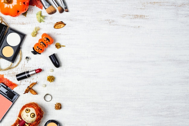 Weibliche kosmetik der flachen lage im herbst- und halloween-festivalhintergrund