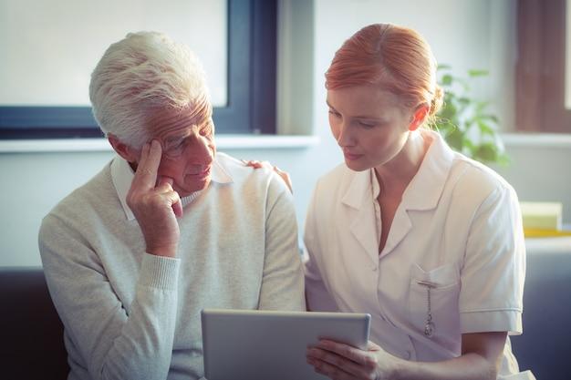 Weibliche krankenschwester, die dem älteren mann ärztlichen attest über digitale tablette zeigt