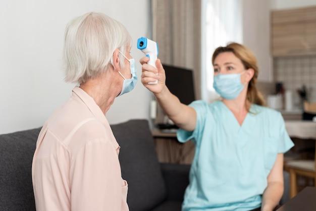 Weibliche krankenschwester, die die temperatur der älteren frau prüft
