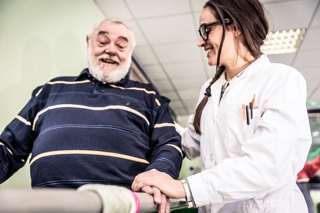 Weibliche krankenschwester, die für älteren mann sorgt