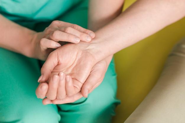 Weibliche krankenschwester, die herzschlag des patienten überprüft