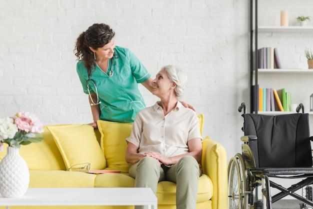 Weibliche krankenschwester, die ihren älteren geduldigen sitzen auf sofa tröstet