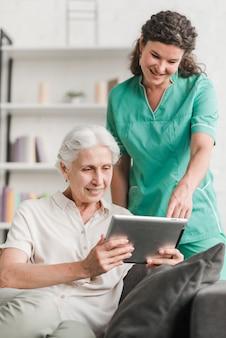 Weibliche krankenschwester mit ihrem aufpassenden video des patienten auf digitaler tablette