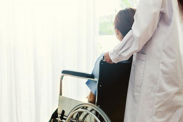 Weibliche krankenschwester oder doktor, die patienten auf einen rollstuhl im krankenhaus für hilfesupport drücken