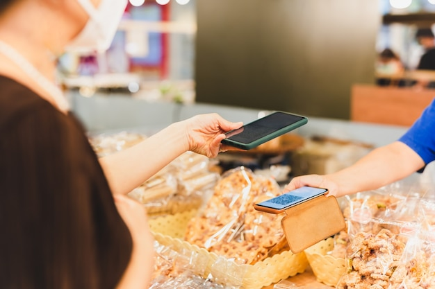 Weibliche kunden in schutzmaske machen kontaktlose verkaufsfrau für mobile zahlungen im einzelhandelsgeschäft.