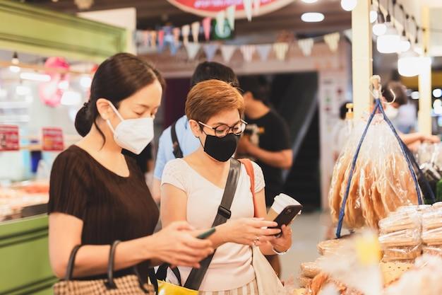 Weibliche kunden in schutzmaske machen kontaktloses mobiles bezahlen im einzelhandelsgeschäft.