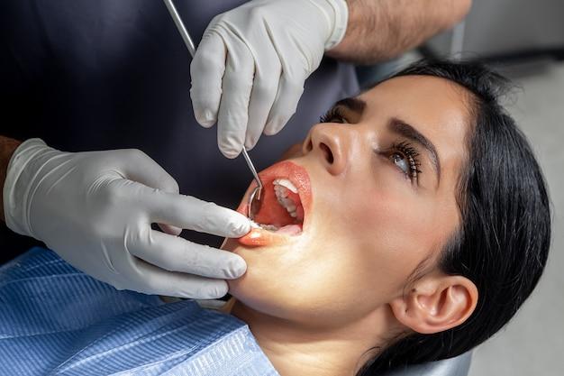 Weibliche kundin mit offenem mund, während ein zahnarzt mit handschuhen und werkzeugen sie in einer klinik untersucht