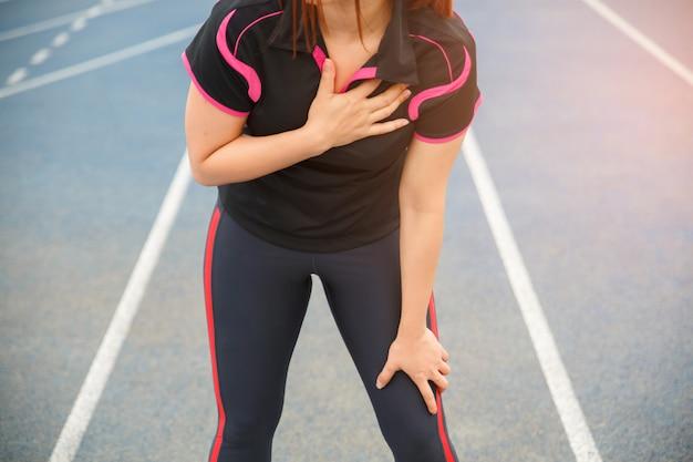 Weibliche läuferathletenbrustverletzung und -schmerz. frau, die unter schmerzlicher brust oder symptomen der herzkrankheit leidet.