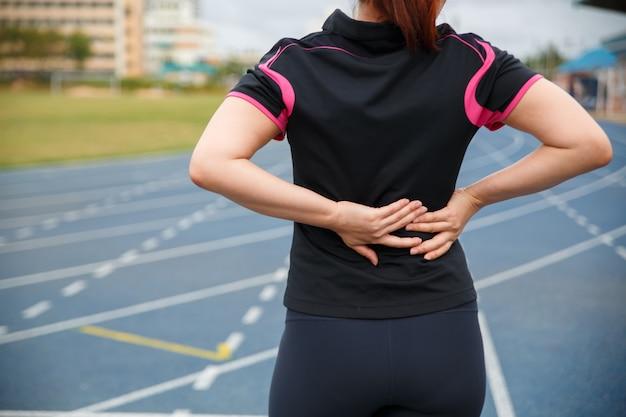Weibliche läuferathletenrückenverletzung und -schmerz. frau, die unter schmerzlichem hexenschuss beim laufen auf der blauen gummierten laufbahn leidet.