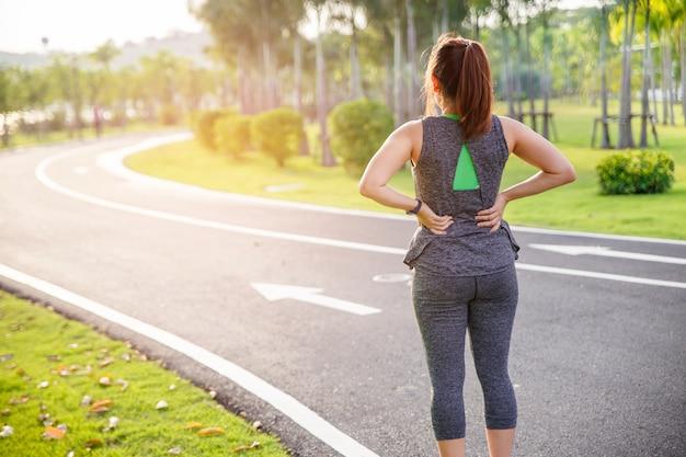 Weibliche läuferathletenrückenverletzung und -schmerz. frau, die unter schmerzlichem hexenschuss beim morgens laufen leidet.