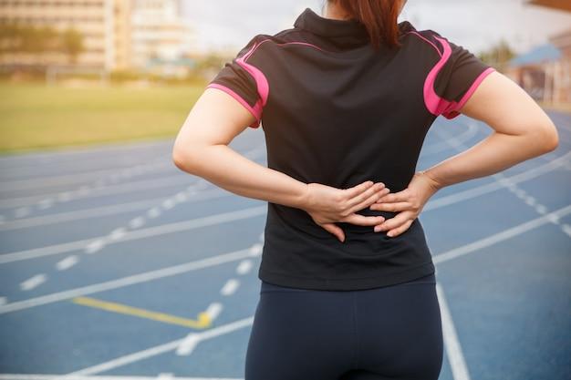 Weibliche läuferathletenrückenverletzung und -schmerz. frau, die unter schmerzlichem hexenschuss leidet.