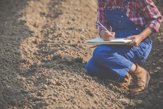 Weibliche landwirte erforschen den boden.