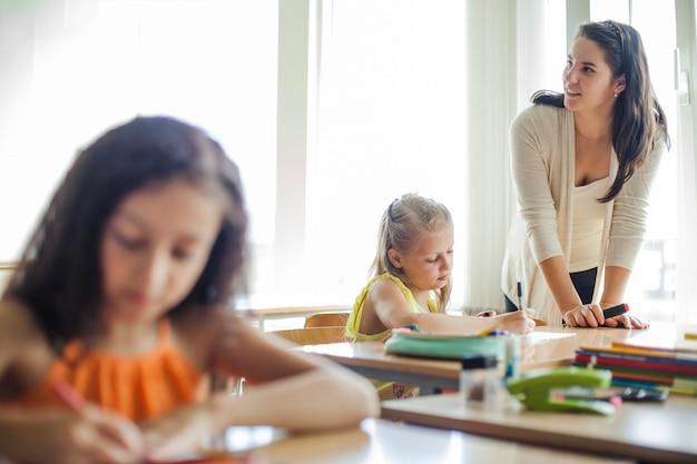 Weibliche lehrer lehnt auf tisch wegschauen