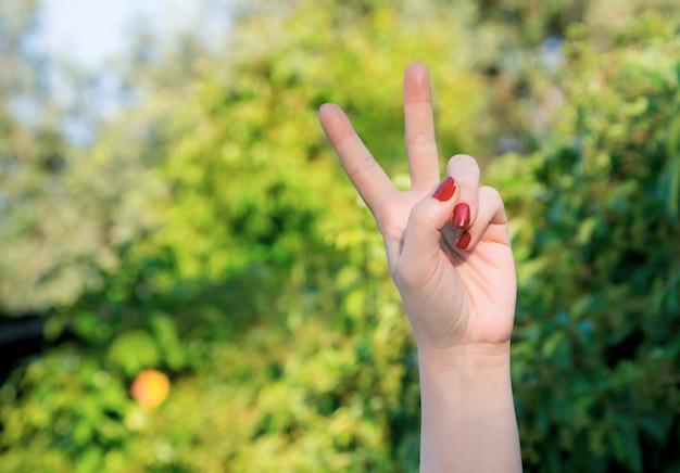 Weibliche linke hand mit roten nägeln, die sieg und friedensgeste tun