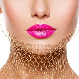 Weibliche lippen mit rosa lippenstift und goldenem schleier am hals. nahansicht.