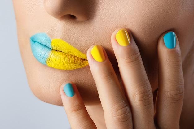 Weibliche lippen mit zwei verschiedenen lippenstiften und bunten nägeln