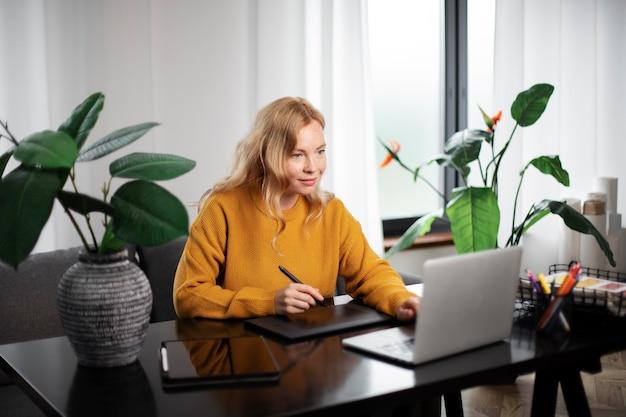 Weibliche logo-designerin, die an ihrem tablet arbeitet, das mit einem laptop verbunden ist