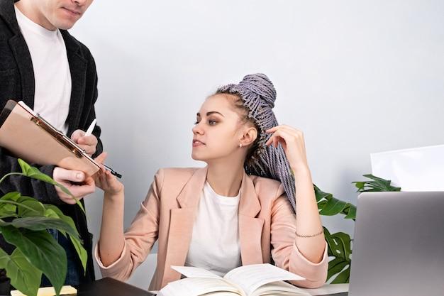 Weibliche macht, regisseurin, geschäftskonzept. junge selbstbewusste schöne frau gibt anweisungen, um mann unterzuordnen, während im büro am schreibtisch und am laptop sitzen. moderne frau, die kanekalon-zöpfe trägt