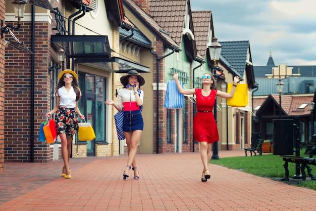 Weibliche mädchen der recht glücklichen hellen frauen in den bunten kleidern, in den hüten und in den hohen absätzen mit einkaufstaschen gehend an der straße nach dem einkauf