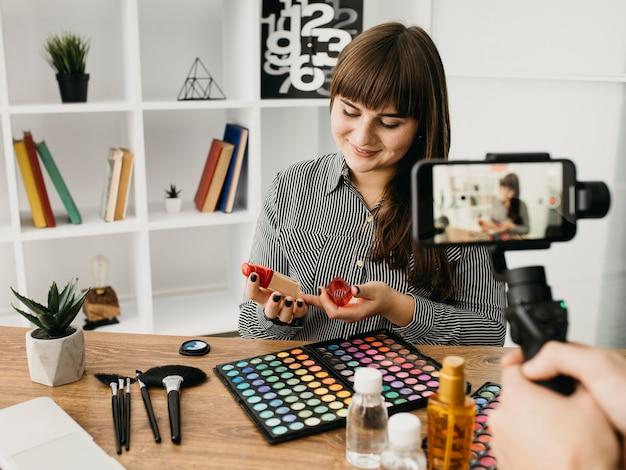 Weibliche make-up-bloggerin mit streaming mit smartphone zu hause