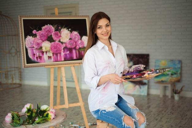 Weibliche malerzeichnung im kunststudio unter verwendung des gestells.