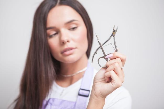 Weibliche maniküre mit nagelhautzange und schere