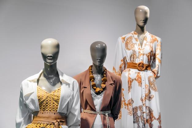 Weibliche mannequins, die in der schaufensteranzeige des freizeitbekleidungsshops der frauen im einkaufszentrum stehen