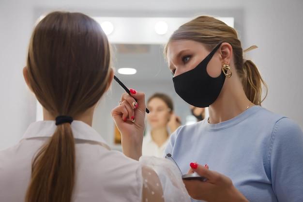 Weibliche maskenbildnerin macht süße schöne junge frau im schönheitssalon. kundendienst