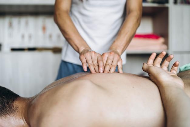 Weibliche masseuse gibt dem mann rückenmassage, der auf der massageliege liegt