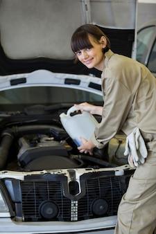 Weibliche mechaniker gießt öl schmiermittel in den automotor