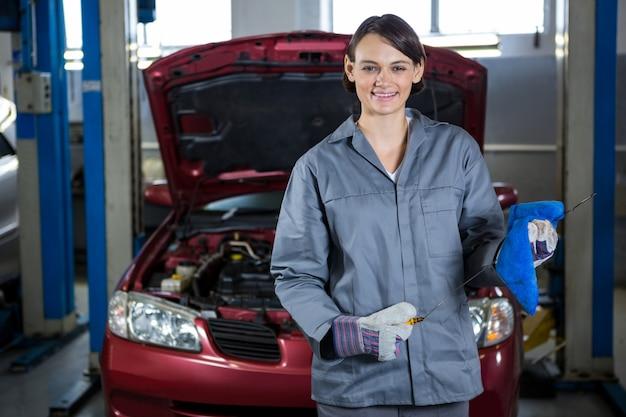 Weibliche mechaniker halte peilstab